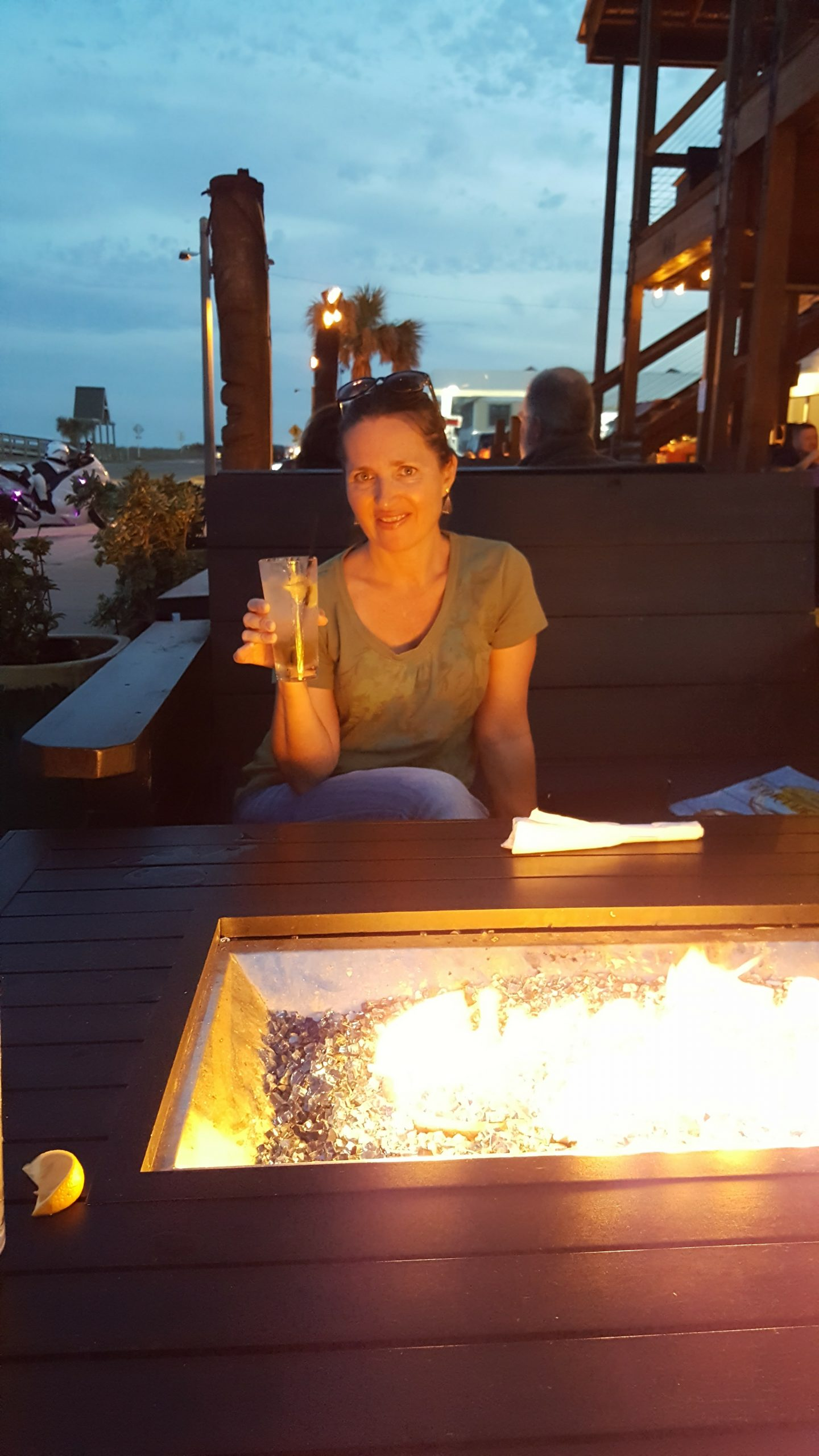 shows Donnamarie at a fireside table with a cocktail